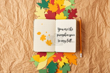 "top view of notebook with ""you are the pumpkin spice to my fall"" lettering, pencil and colorful handcrafted paper leaves on crumpled paper background"