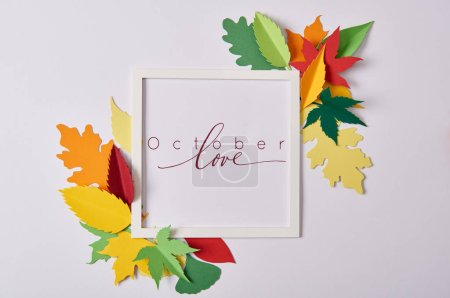 "flat lay with handcrafted paper leaves and empty frame with ""october love"" inspiration on white tabletop"
