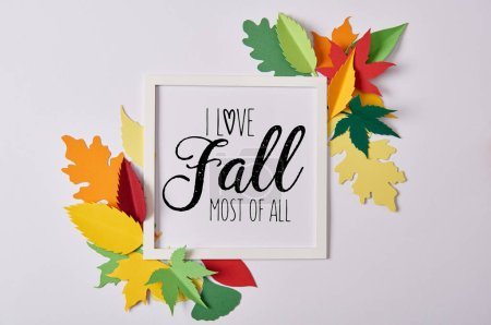 "flat lay with handcrafted paper leaves and empty frame with ""I love fall most of all"" inspiration on white table"