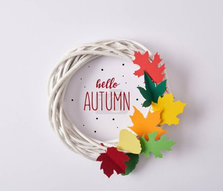 """top view of handmade wreath with colorful paper foliage and """"hello autumn"""" lettering on white backdrop"""