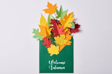 """Photo for Top view of colorful handcrafted paper leaves in green envelope with """"welcome autumn"""" lettering on white background - Royalty Free Image"""
