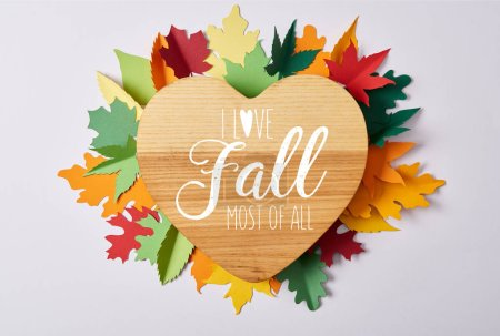 "top view of wooden heart shaped board and colorful handcrafted leaves on white surface with ""I love fall most of all"" lettering"