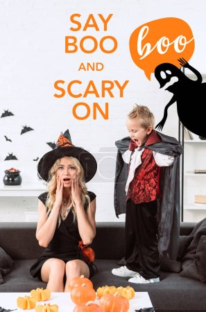 "little boy in vampire costume screaming at mother in witch halloween costume at home with ""say boo and scary on"" lettering"