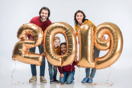 smiling parents with siblings holding sign 2019 made of golden balloons for new year isolated on white background
