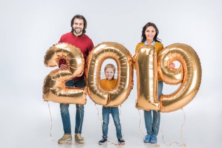 smiling parents with son holding sign 2019 made of golden balloons for new year isolated on white background