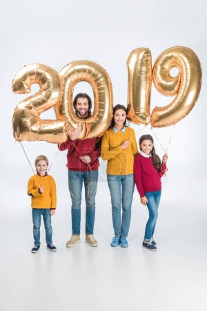 smiling family holding sign 2019 made of golden balloons for new year isolated on white background