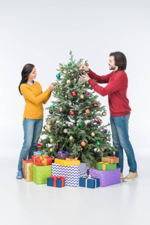 couple decorating christmas tree with glass balls isolated on white