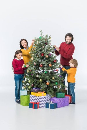 Happy family decorating christmas tree with presents isolated on white