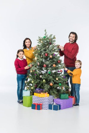 Happy family decorating christmas tree with glass balls and looking at camera isolated on white
