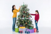 smiling mother with daughter decorating christmas tree with glass balls isolated on white