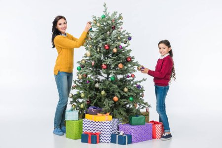 Happy mother with daughter decorating christmas tree with glass balls and looking at camera isolated on white
