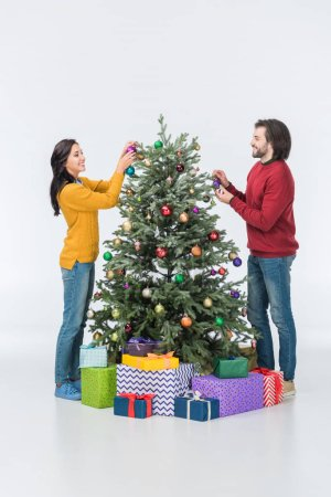 smiling couple decorating christmas tree with glass balls isolated on white