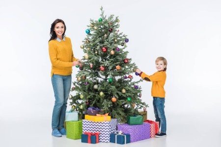 Happy mother with son decorating christmas tree with glass balls and looking at camera isolated on white
