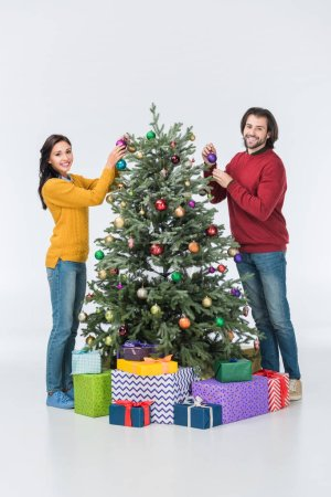 Happy couple decorating christmas tree with glass balls isolated on white