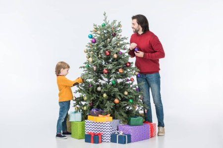father with son decorating christmas tree with glass balls and presents isolated on white