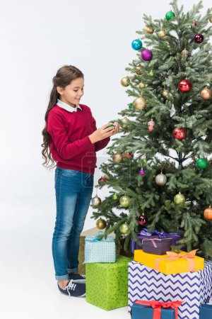 Happy child decorating christmas tree with presents isolated on white