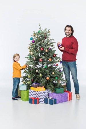 Photo pour Heureux père et fils décoration arbre de Noël avec des cadeaux isolé sur blanc - image libre de droit