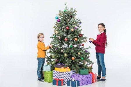 Photo pour Sourire de frères et sœurs décoration arbre de Noël avec présente isolés sur blanc - image libre de droit
