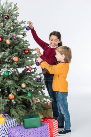 Happy siblings decorating christmas tree with presents isolated on white