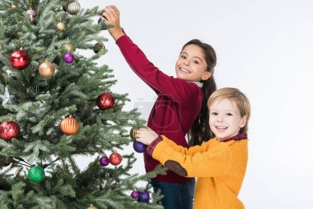 Happy siblings decorating christmas tree with glass balls isolated on white