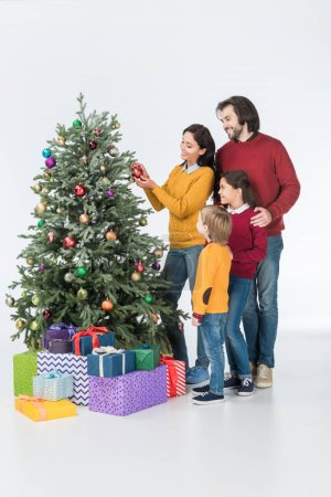 family standing near mother decorating christmas tree with presents isolated on white