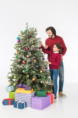 smiling father with daughter decorating christmas tree with presents isolated on white