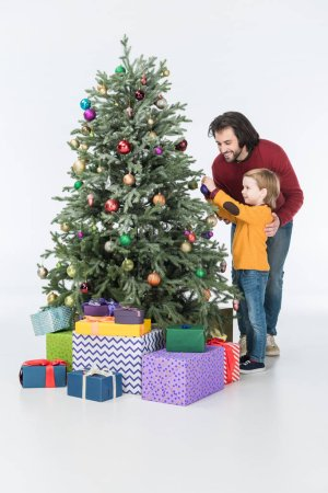 smiling father with son decorating christmas tree with presents isolated on white