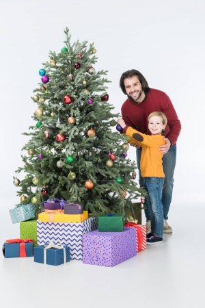 Happy father with son decorating christmas tree with presents isolated on white