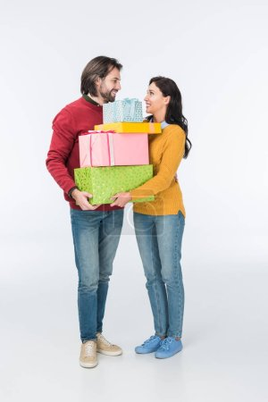 smiling couple with wrapped gifts looking at each other isolated on white