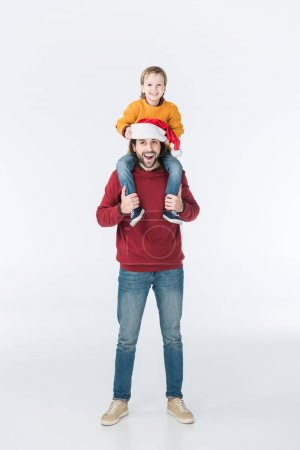 happy father in santa hat carrying son on shoulders isolated on white