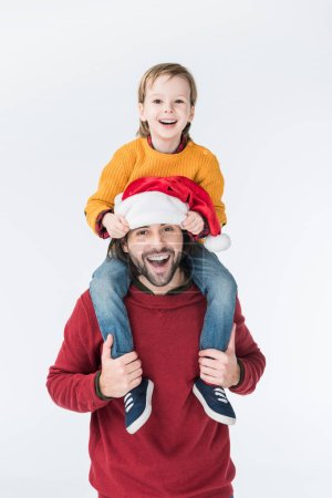 smiling father in santa hat carrying son on shoulders isolated on white