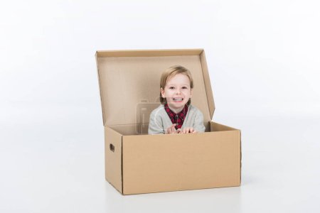 Photo for Smiling boy sitting in cardboard box isolated on white - Royalty Free Image