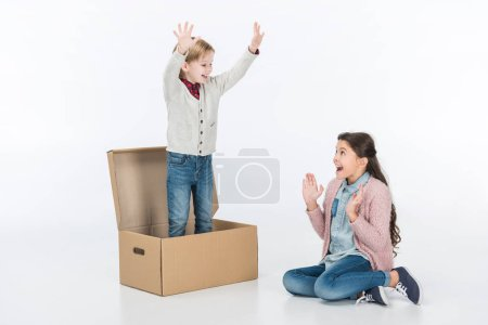Surprised kid with boy standing in cardboard box isolated on white