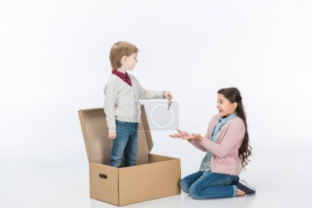 boy giving key from new house to surprised sister ready to move into new house isolated on white