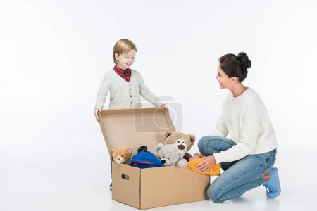 Happy mother with son sitting near cardboard box with toys isolated on white