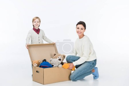 smiling mother with son sitting near cardboard box with toys and looking at camera isolated on white