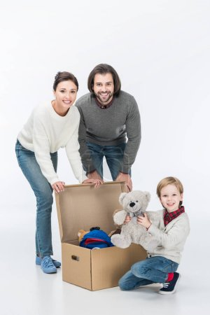 Happy parents with son holding teddy bear looking at camera isolated on white