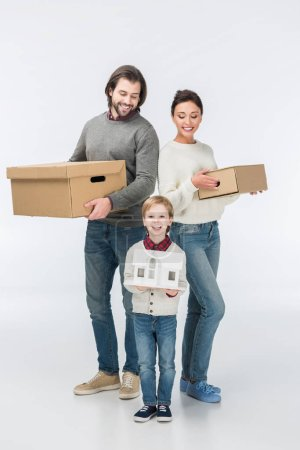 Photo for Little smiling boy holding carton house ready to move with his family into new house isolated on white - Royalty Free Image