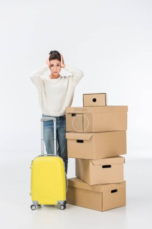 Photo for Stressed woman with suitcase and cardboard boxes moving to new house isolated on white - Royalty Free Image