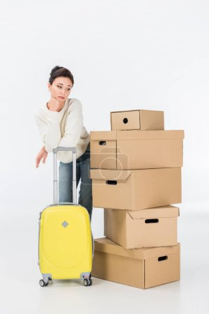 Photo for Pensive woman with suitcase and cardboard boxes moving to new house isolated on white - Royalty Free Image