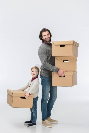father holding stack of cardboard boxes and son helping him isolated on white