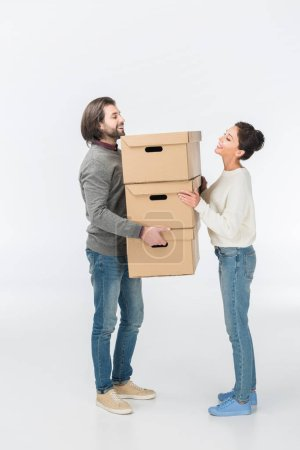 smiling couple holding stack of cardboard boxes isolated on white