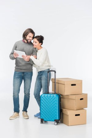 happy couple using digital tablet standing near blue suitcase and carton boxes isolated on white