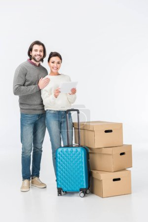 Photo for Couple using digital tablet standing near suitcase and carton boxes and looking at camera isolated on white - Royalty Free Image