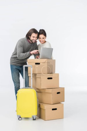 Photo for Smiling couple using laptop on cardboard boxes isolated on white - Royalty Free Image
