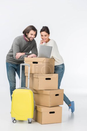 couple using laptop on cardboard boxes isolated on white