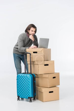 man using laptop on cardboard boxes isolated on white