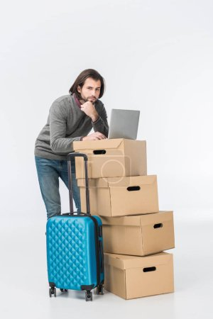 Photo for Pensive man using laptop on cardboard boxes isolated on white - Royalty Free Image