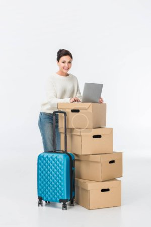 Photo for Smiling woman using laptop on cardboard boxes isolated on white - Royalty Free Image