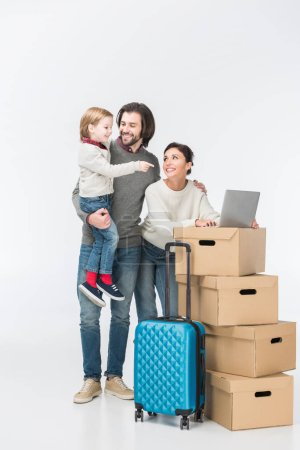 family using laptop on cardboard boxes and son showing on laptop isolated on white